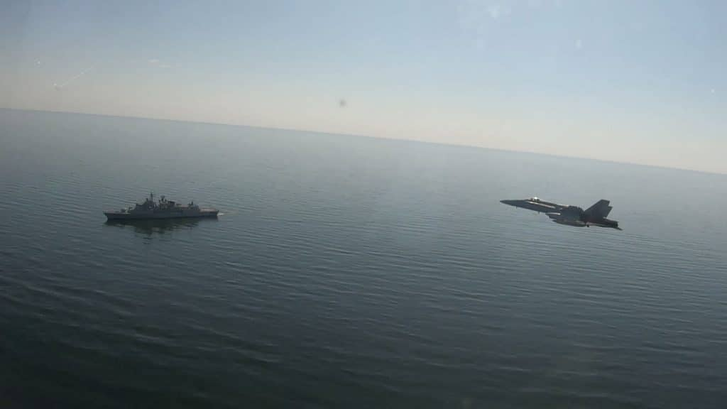 A Spanish Air Force (Ejército del Aire) F-18 fighter flies over Portuguese Navy Vasco da Gama-class frigate NRP Corte-Real (F332