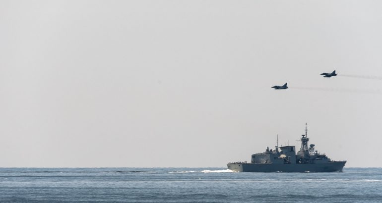 Two French Air Force (Armée de l'Air) Mirage 2000-5 fighters conducting a low level pass above Royal Canadian Navy Frigate HMCS Toronto